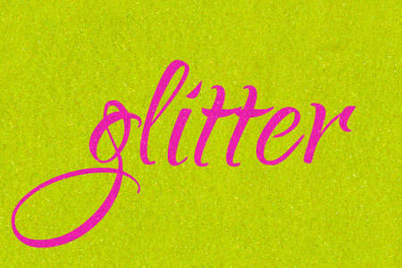 Glitter lettering word neon pink on golden lime sparkle texture. Shiny background 版權商用圖片