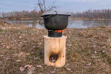 Cauldron cooking on Finnish (Swedish) log candle at river coast 版權商用圖片