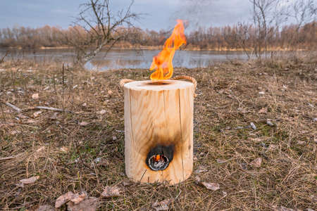 Vertical fire of Finnish (Swedish) log candle at river coast