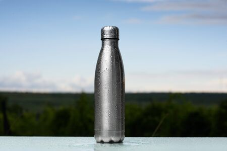 Thermos bottle sprayed with water. Against the sky background. Water tumbler.