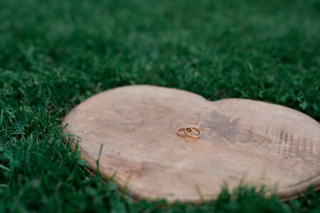 Wedding rings on a heart-shaped wood placed on the grass. Stock Photo