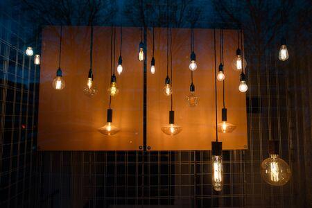 Many creative lamps illuminate the window at night.