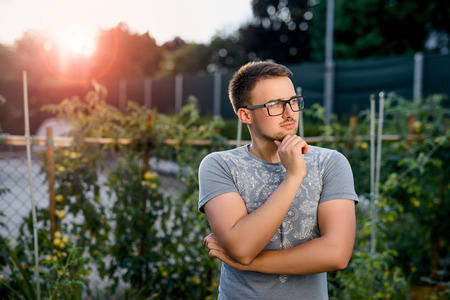 Pensive young guy in the park at sunset. Stock Photo