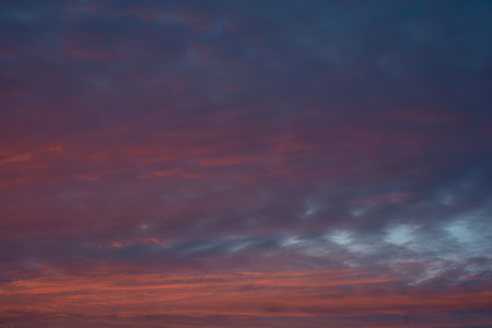 Dramatic colorful sunset sky with clouds. Blue background.