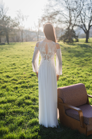 Beautiful bride on sunset in park, back view. Nearby is an old chair. Stock Photo
