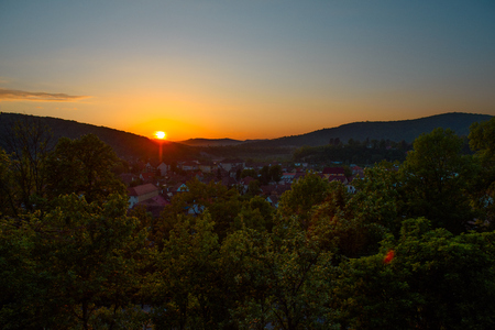 Beautiful landscape of sunrise over small town in forest mountains. Romania, Sighisoara - 2016.