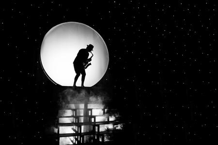 Silueta de un músico con un saxofón sobre un fondo blanco en forma de un círculo en el espacio negro. BW foto. Foto de archivo - 90811015