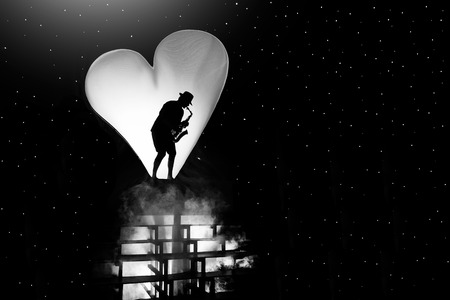 Silhouette of a musician with a saxophone against a white background in the form of a heart in black space. BW photo.