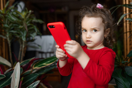 Surprised child with smartphone dressed in red inside at home. Stock Photo