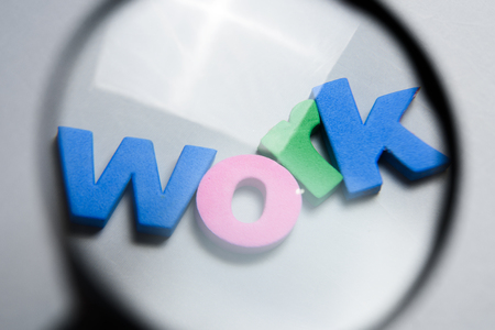 WORK, word written on white background with colorful letters under magnifying glass. Stock Photo