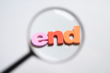 END, word written on white background with colorful letters under magnifying glass. Stock Photo
