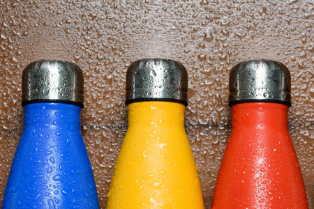 Colorful stainless flask bottles on a wooden table sprayed with water