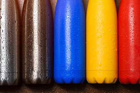 Colorful stainless  bottles, on a wooden table sprayed with water. Matte red bottle, blue, yellow and platinum color. With sunlight effect 写真素材