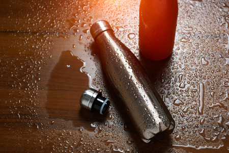 Two stainless  bottles on a wooden table sprayed with water. With sunlight effect