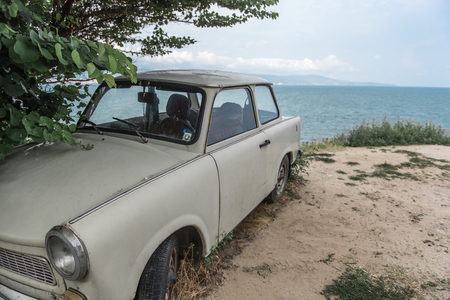 Abandoned vintage european car on sea shore