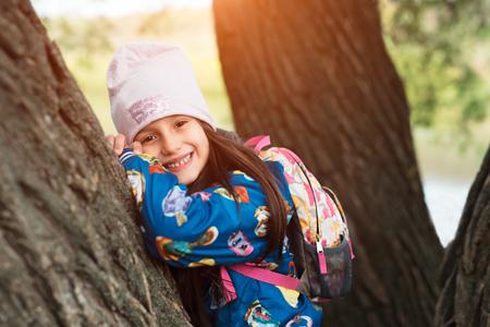Smiling kid girl in park after school 版權商用圖片