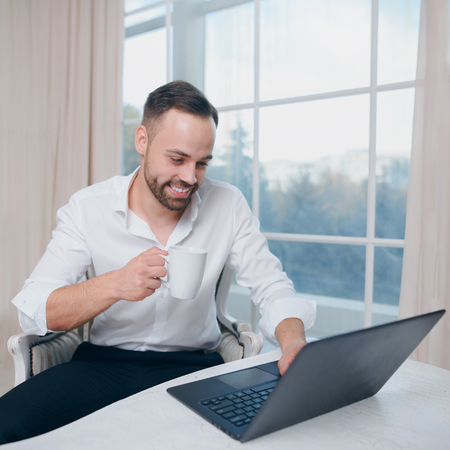 Businessman with coffee in hand, use laptop on window background