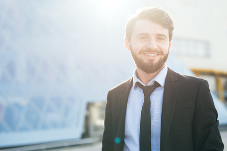Modern hipster bearded businessman on skyscraper background Stock Photo
