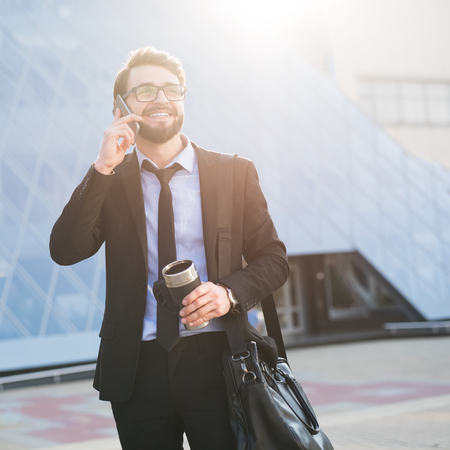Successful and young businessman with coffee and smartphone in hands on office build background with sunlight