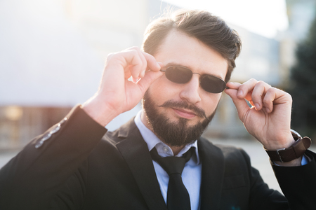 Portrait of bearded hipster with sunglasses dressed in suit.