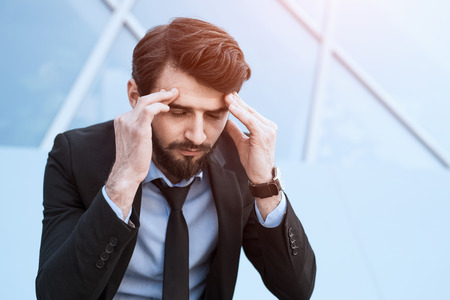 Sad bearded businessman in suit near office build.