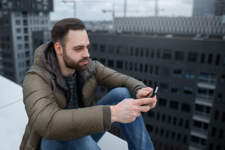 Bearded hipster guy looks at the social network in the smartphone, on the roof of a tall building.