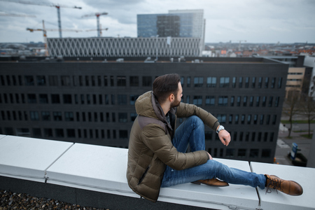 Modern bearded hipster looking at the city from roof of building.