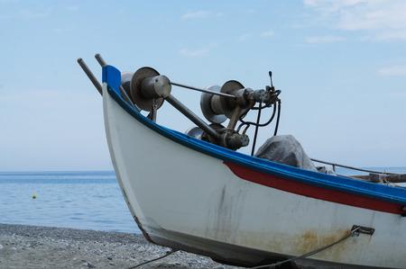 Abandoned fishing boat on beach near sea.