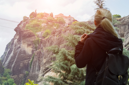 Back view of blonde girl in black with backpack in mountains at sunset.