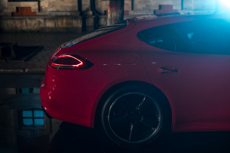 Back view of red modern sport car, after rain in night city. Stock Photo