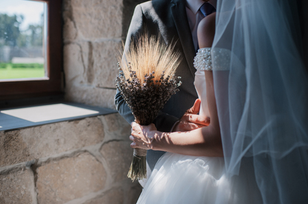 Bridal bouquet of wheat and lavender in bride hand.