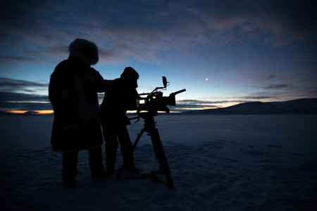Silhouette of people who filming sunset in desert of Siberia. 写真素材