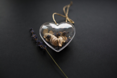 Valentines day background. Glass heart and lavender flower on black background. Фото со стока