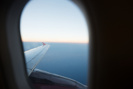 View of airplane wing through window. Flying above the clouds Archivio Fotografico