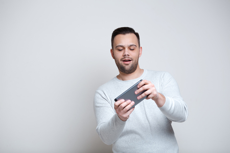 Happy adult man playing video games on smartphone over white background. Stock Photo