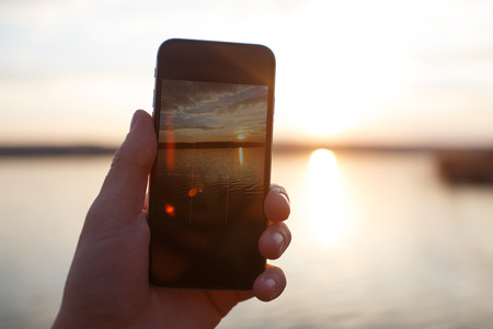 Male hand holding smartphone and taking the photo of sunset. Stock Photo
