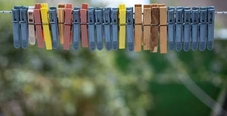 Colorful clothespins outdoor, on the rope over blur background.