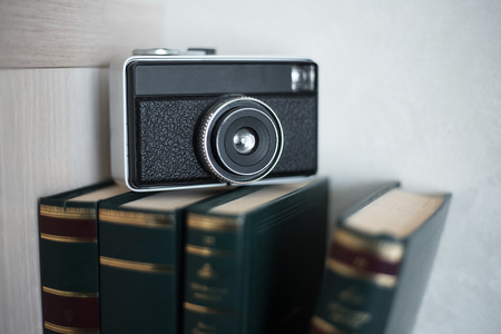 Books and vintage camera over white background.