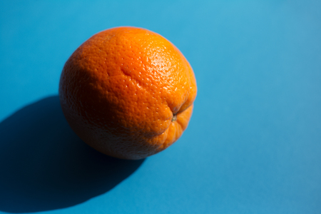 Orange fruit over blue background with shadow. 写真素材