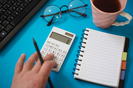 Man using calculator to calculate on office desk.