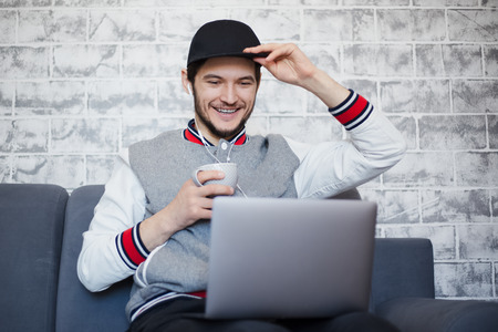 Happy student guy using laptop with cup of coffee.