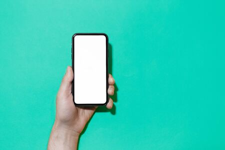 Close-up of male hand holding smartphone with mockup isolated on background of Aqua Menthe color.