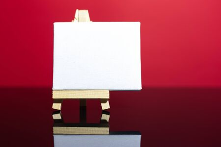 Close-up of small easel with white mockup on paper, on glass desk and red background.