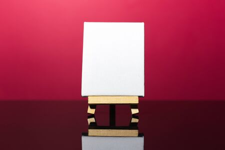 Close-up of small easel with white mockup on dark coral pink background. Фото со стока