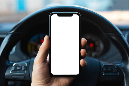 Close-up of male hand holding smartphone with white mockup on screen, background of car steering wheel.