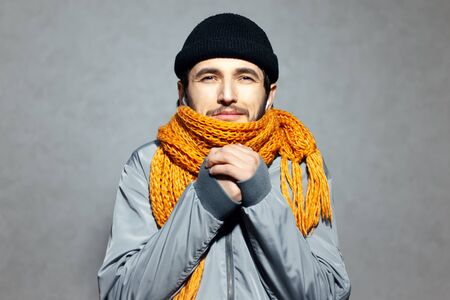 Portrait of young man who feels cold, wearing orange scarf and black beanie hat, on gray background.