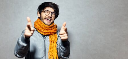 Portrait of happy man pointing fingers on camera, wearing glasses and orange scarf with grey bomber.