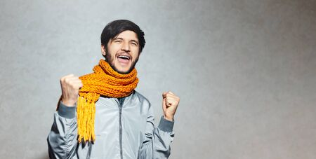 Portrait of happy successful young man, wearing orange scarf with grey bomber. Standard-Bild