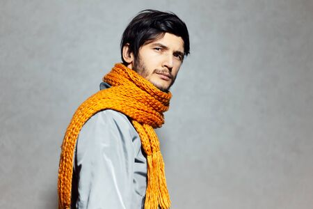 Portrait of young man with orange scarf and grey bomber.