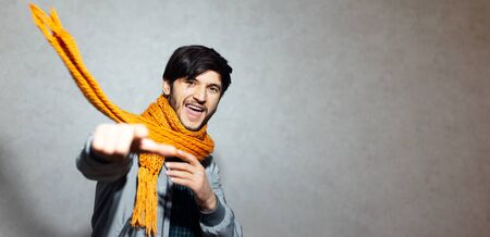 Portrait of happy man pointing finger on camera, wearing orange scarf with grey bomber. Standard-Bild